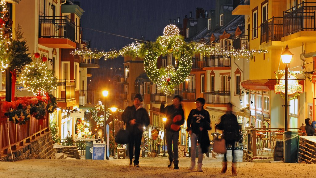 Mont-Tremblant Ski Resort showing night scenes and a city as well as a small group of people