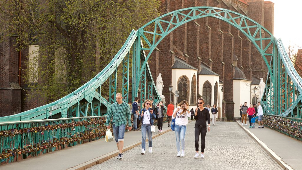Wroclaw showing a bridge as well as a small group of people