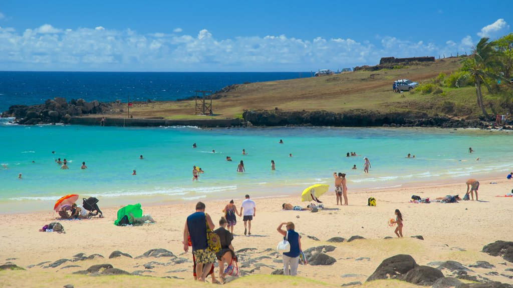Anakena Beach featuring a sandy beach as well as a small group of people