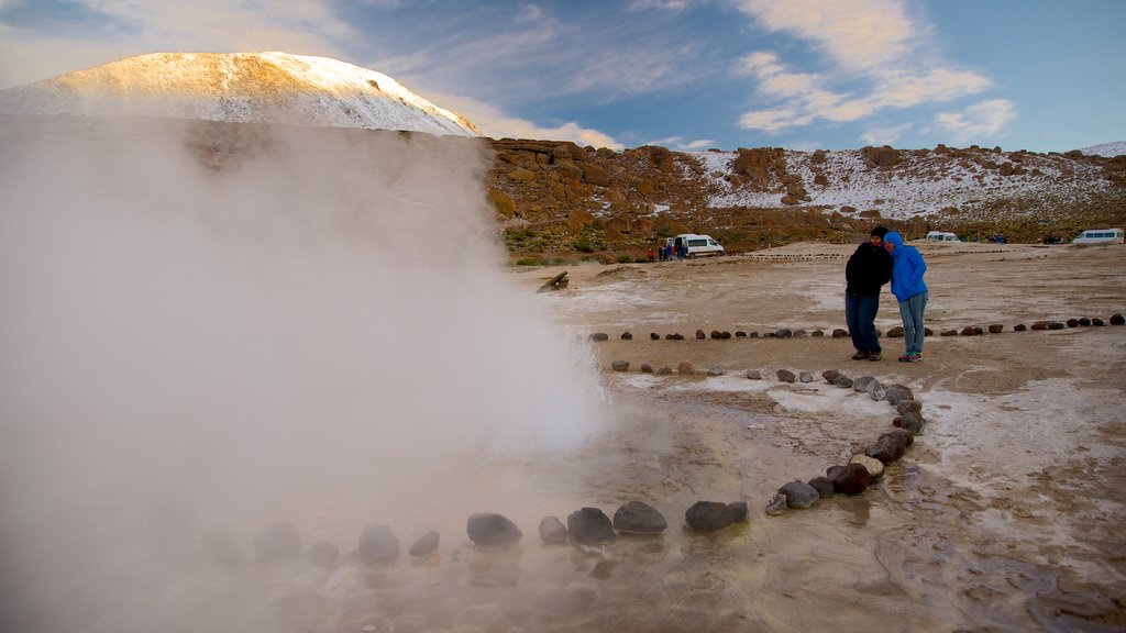 El Tatio Geyser Field featuring desert views as well as a small group of people