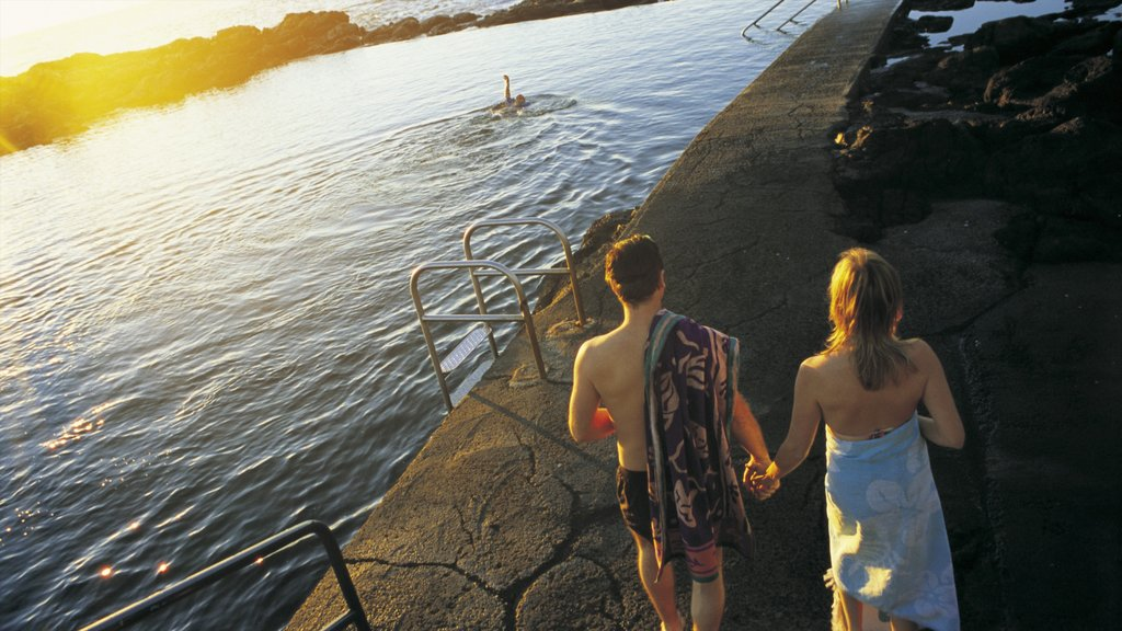 Kiama featuring a lake or waterhole and a sunset as well as a couple