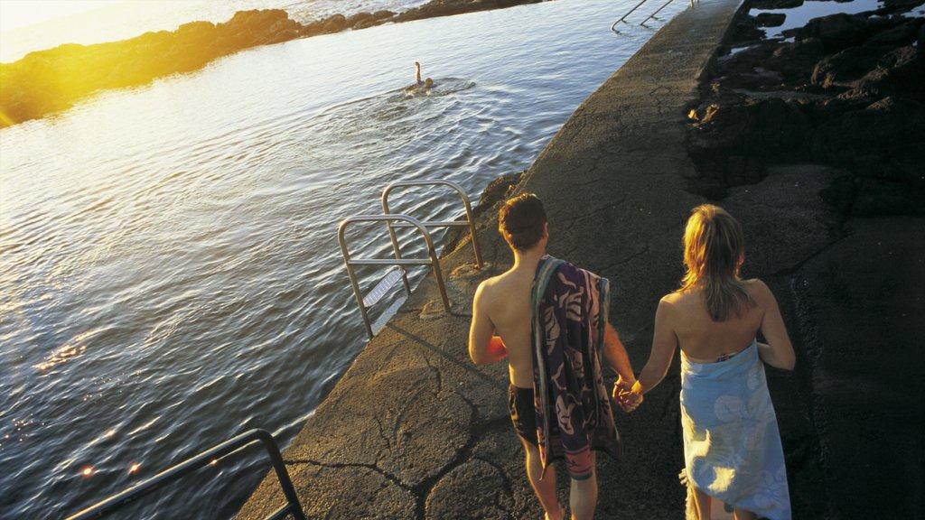 Kiama mostrando una puesta de sol y un lago o abrevadero y también una pareja