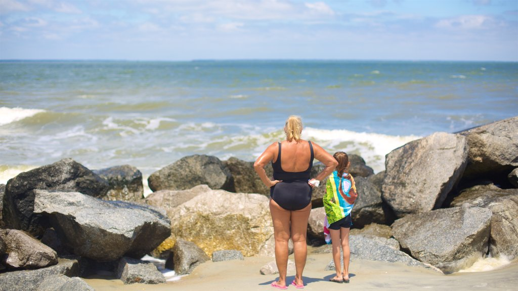 Tybee Island featuring a sandy beach and rugged coastline as well as a family