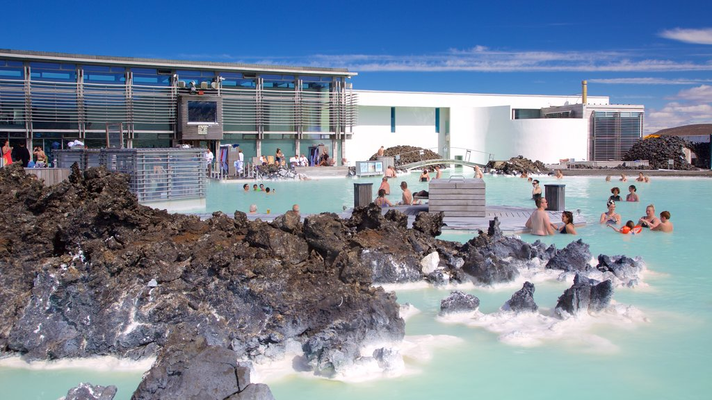 Blue Lagoon showing a luxury hotel or resort and a hot spring as well as a large group of people