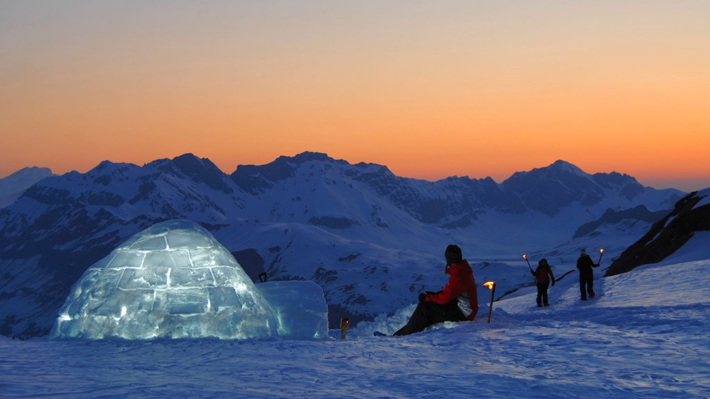 Engelberg-Titlis Ski Resort which includes a sunset and snow as well as a small group of people