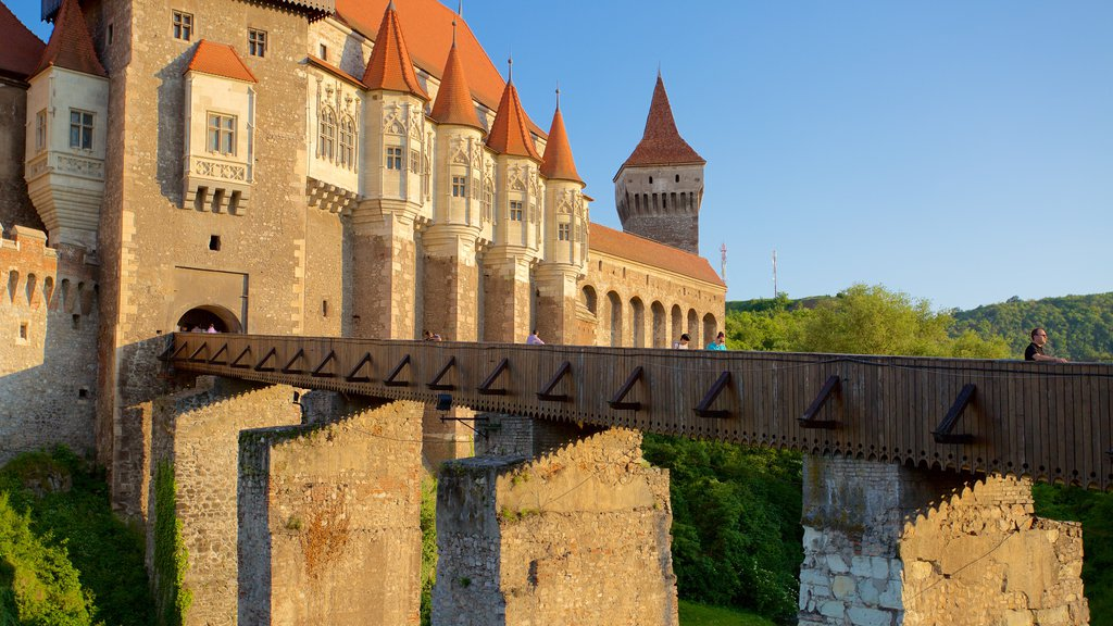 Hunedoara Castle which includes a bridge, a church or cathedral and a sunset