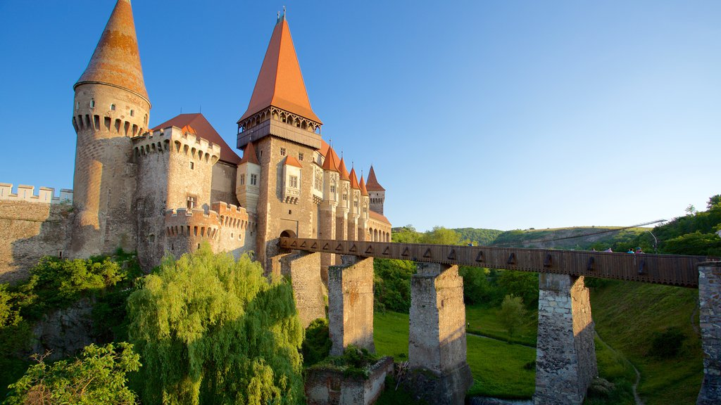 Hunedoara Castle showing a bridge, a sunset and a church or cathedral