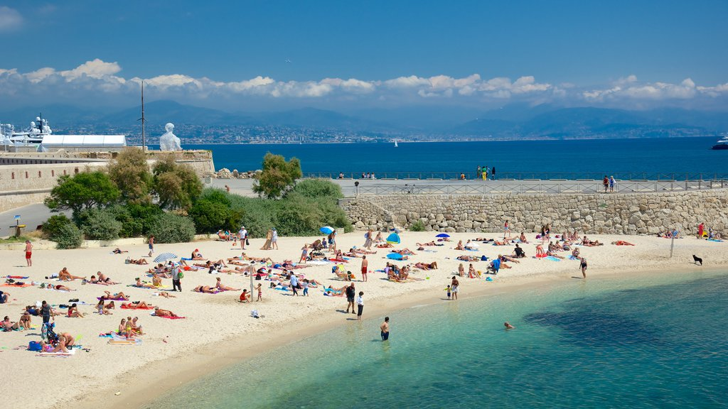 Antibes featuring a sandy beach as well as a large group of people