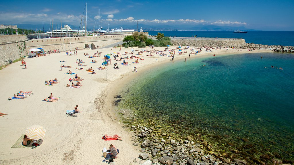 Antibes showing a sandy beach as well as a large group of people