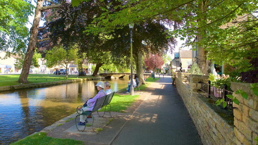 Bourton-on-Water showing a garden and a river or creek as well as a couple