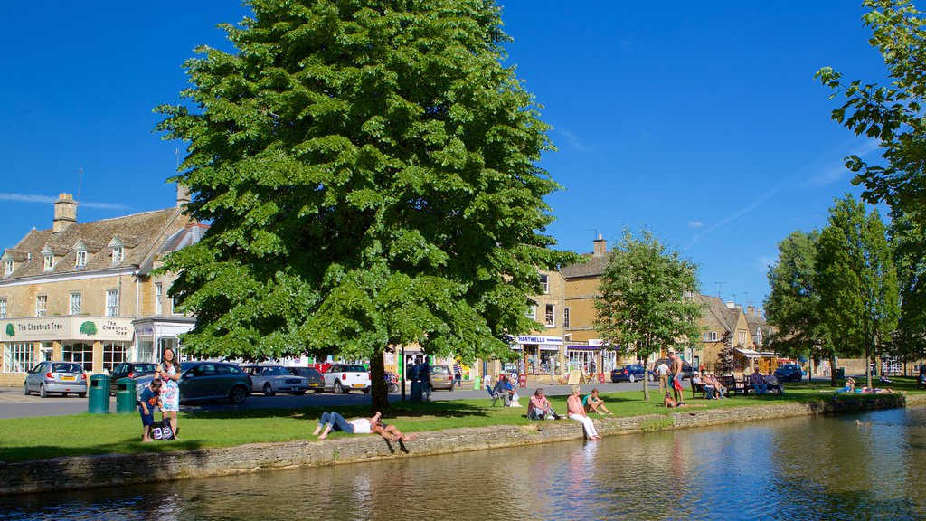Bourton-on-Water featuring a river or creek and a small town or village as well as a small group of people