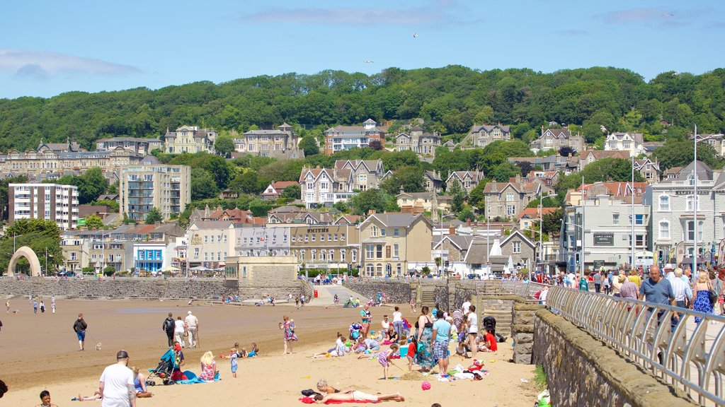 Weston-super-Mare showing a sandy beach and a coastal town as well as a large group of people