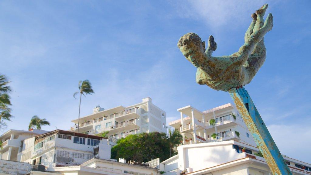 La Quebrada Cliffs showing a statue or sculpture and a coastal town