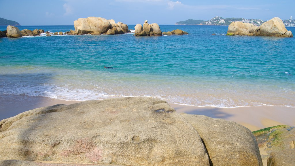 Condesa Beach which includes a sandy beach and rugged coastline