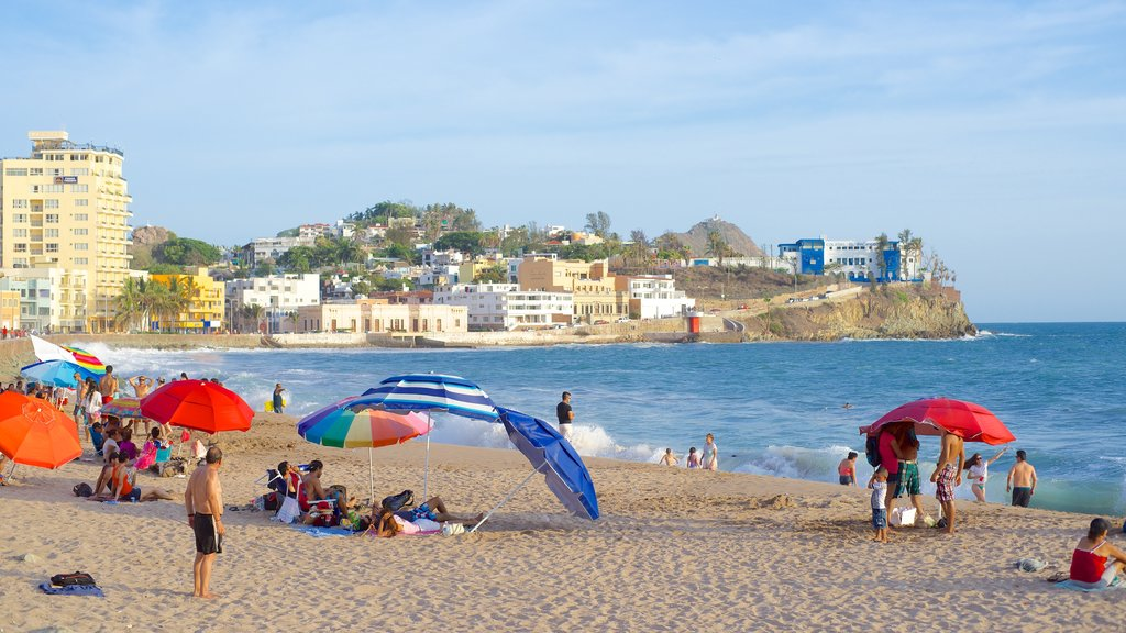Mazatlan showing a beach and a coastal town as well as a large group of people
