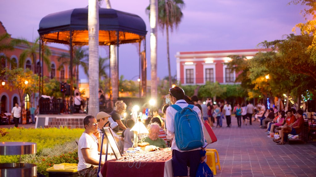 Plaza Machado showing markets and night scenes as well as a small group of people