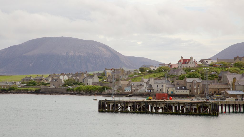 Stromness which includes mountains, a bay or harbor and a coastal town