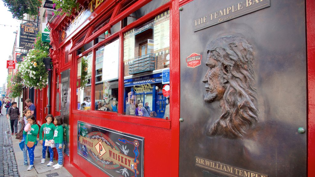 Temple Bar which includes a bar and signage as well as children