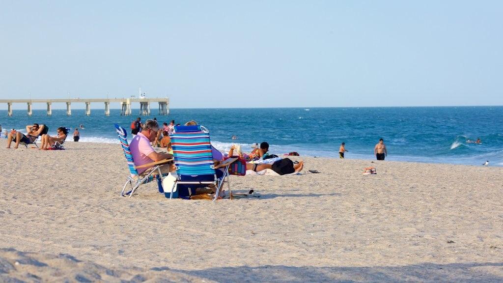 Wrightsville Beach que incluye una playa de arena y también un pequeño grupo de personas