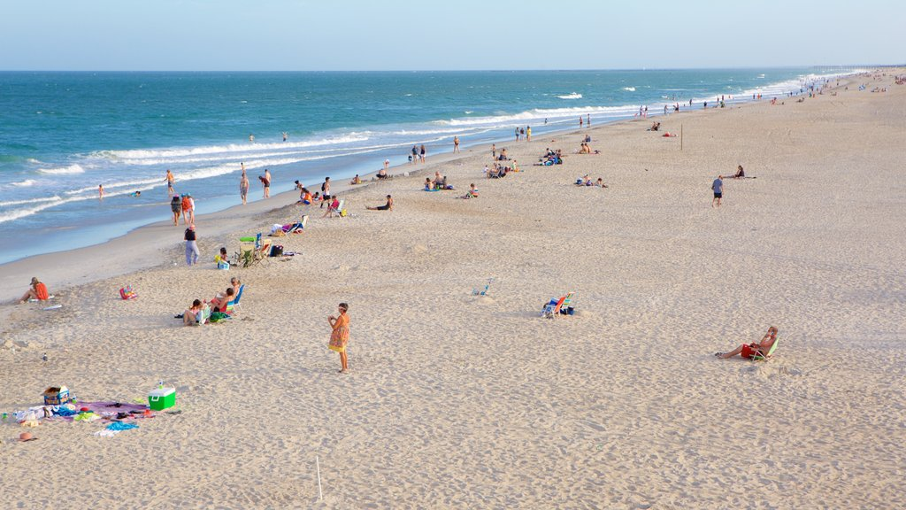 Wrightsville Beach which includes general coastal views and a beach as well as a large group of people