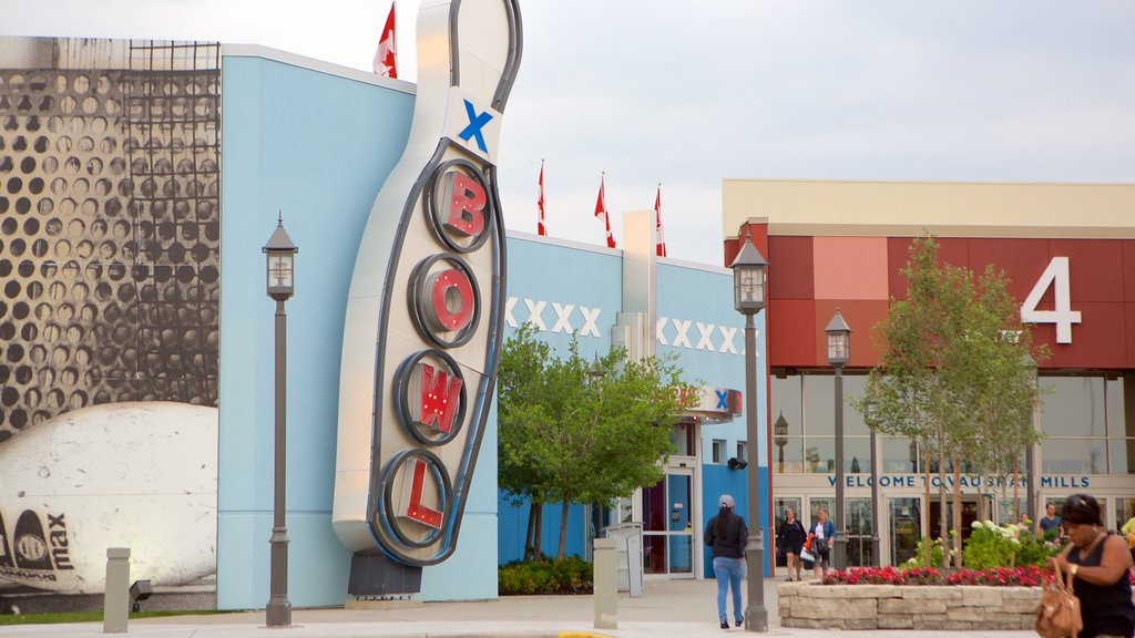 Vaughan Mills Mall showing signage and a square or plaza as well as a small group of people
