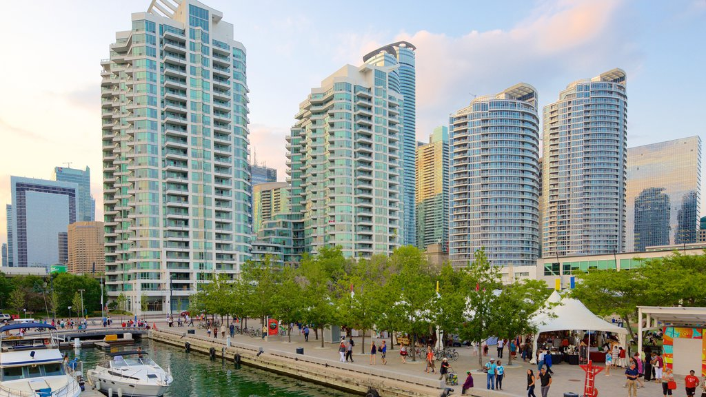Harbourfront showing a marina and a city as well as a large group of people