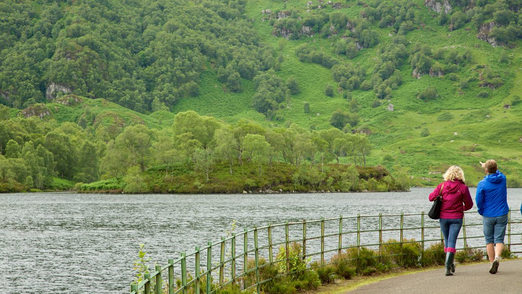 Loch Katrine featuring a lake or waterhole and forests as well as a small group of people