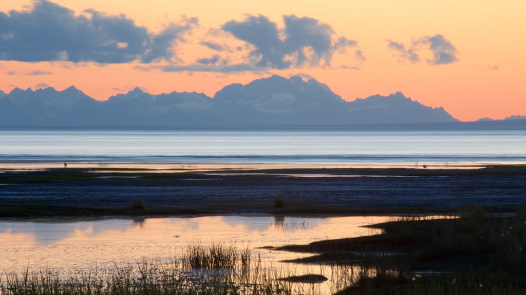 Anchorage featuring a sunset and a beach