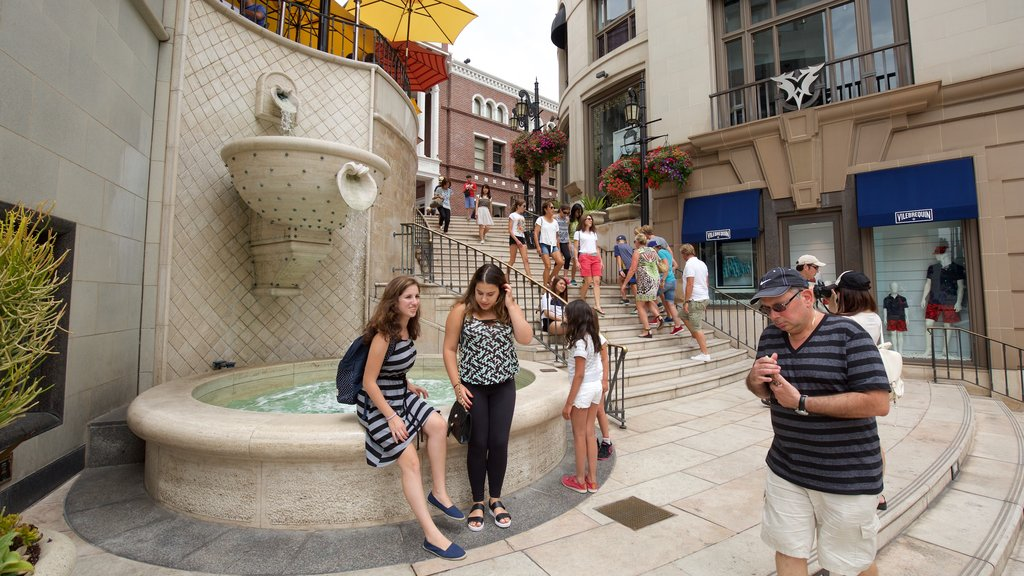 Rodeo Drive which includes a fountain and a pond as well as a large group of people