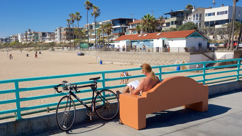 Manhattan Beach featuring a sandy beach and a coastal town as well as an individual male