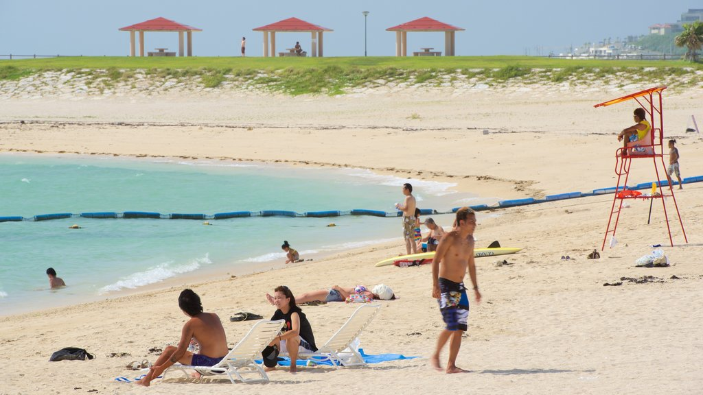 Okinawa showing swimming and a sandy beach as well as a large group of people