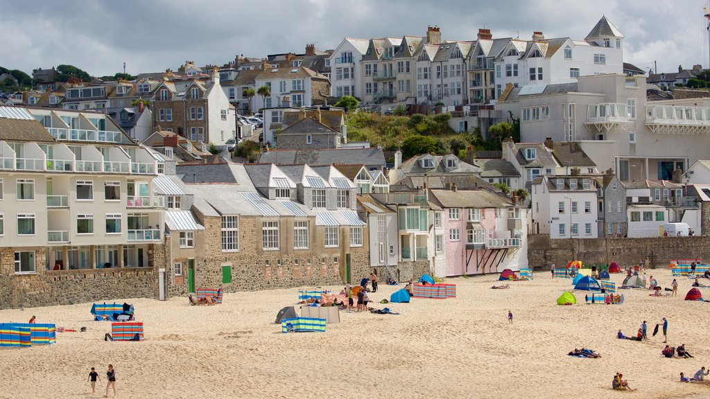 Porthmeor Beach featuring a coastal town and a sandy beach as well as a large group of people