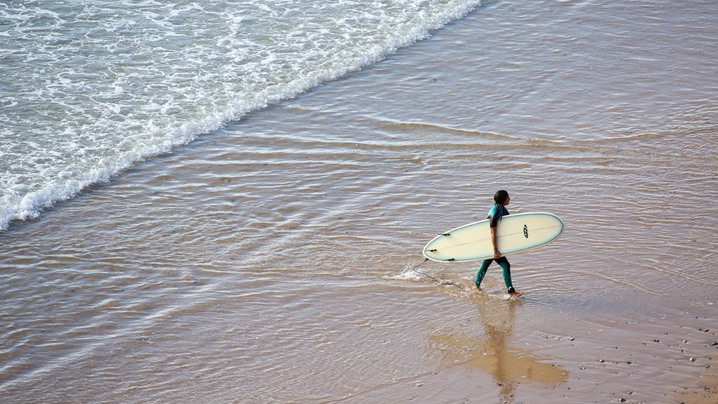 Watergate Bay featuring a beach and surfing as well as an individual male