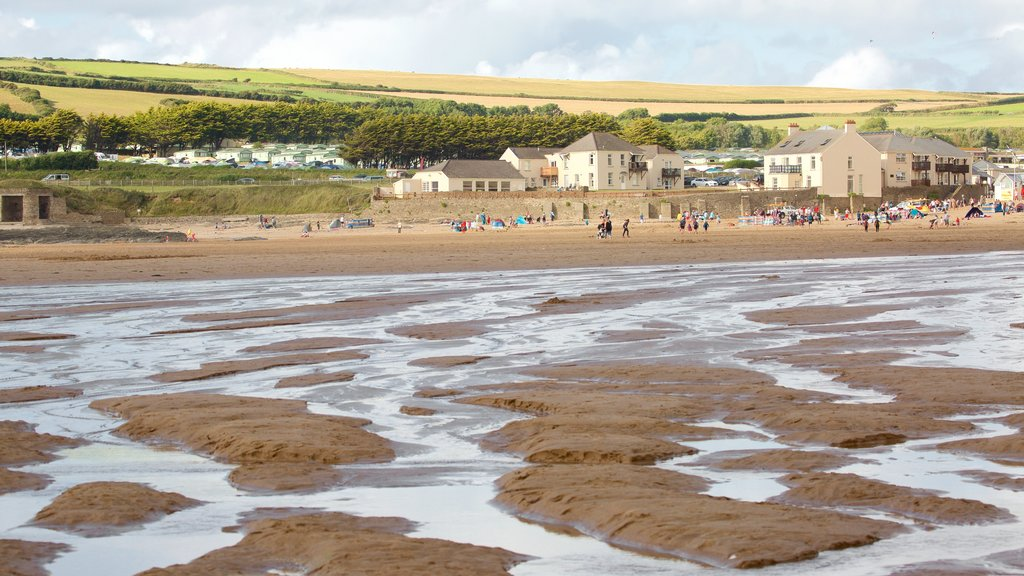 Croyde featuring a sandy beach and a coastal town as well as a large group of people
