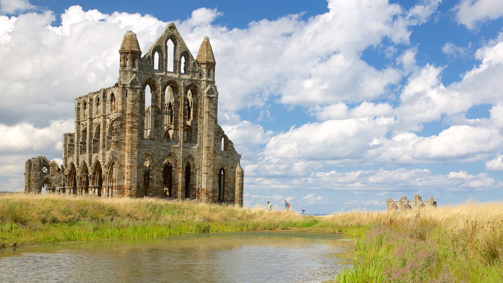 Whitby Abbey showing a river or creek and heritage architecture