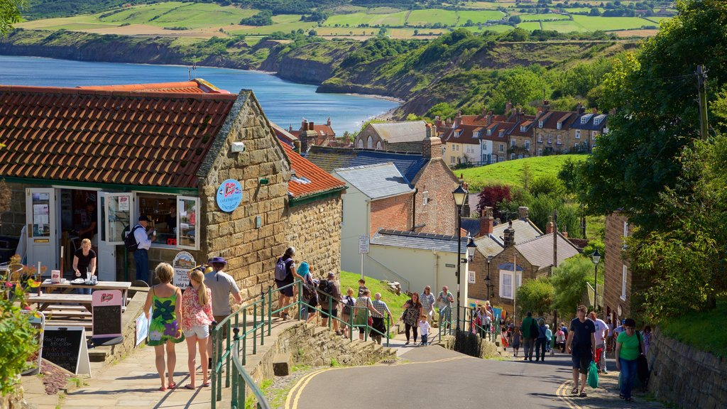 Robin Hood\'s Bay Beach featuring a coastal town and street scenes as well as a large group of people