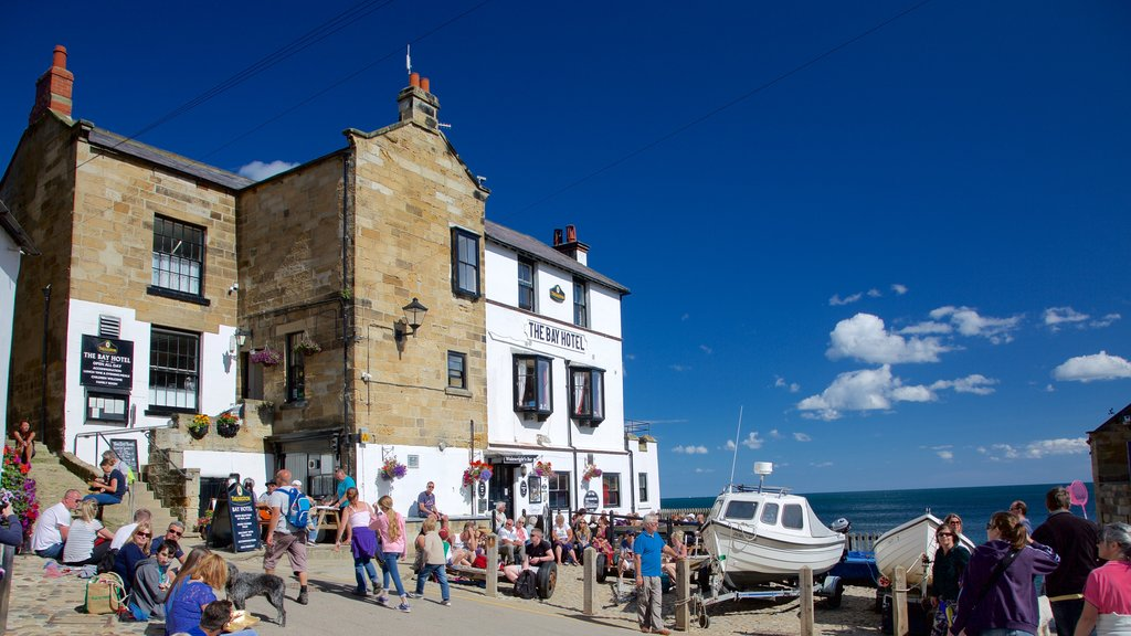 Robin Hood\'s Bay Beach which includes heritage architecture and a coastal town as well as a large group of people
