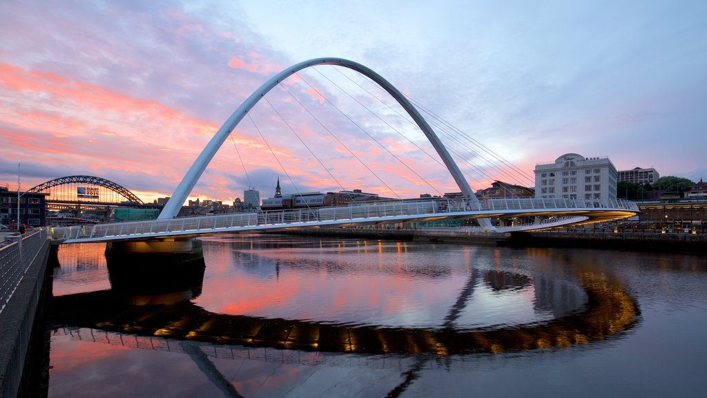 Gateshead Millennium Bridge showing a city, a sunset and a river or creek