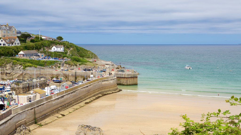 Newquay which includes a coastal town and a sandy beach