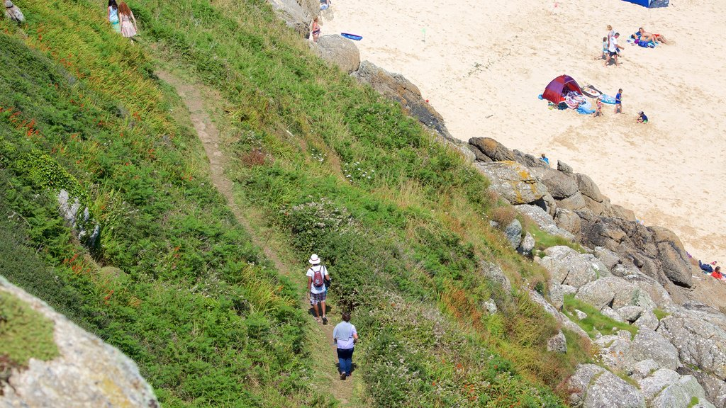 Porthcurno Beach showing a sandy beach and hiking or walking