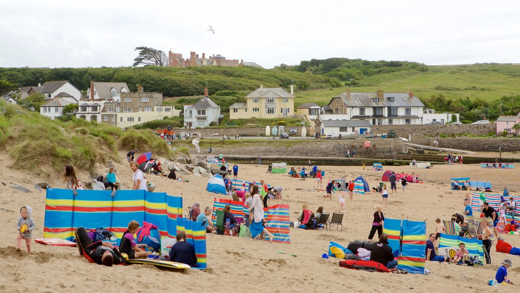 Bude Beach showing a coastal town and a beach as well as a large group of people