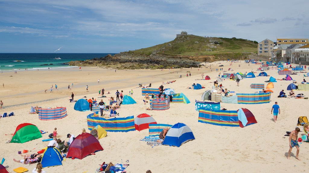 Porthmeor Beach showing a sandy beach as well as a large group of people