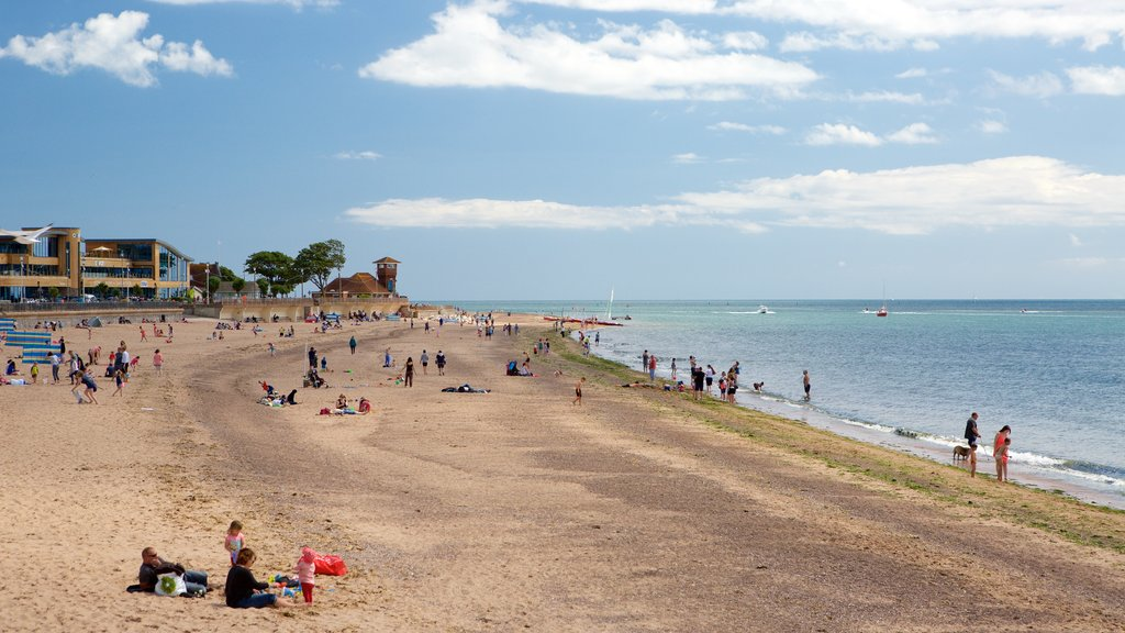 Exmouth featuring a sandy beach as well as a large group of people