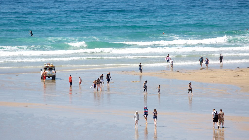 Fistral Beach showing a beach and surf as well as a large group of people