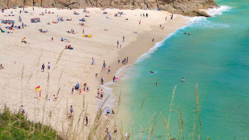 Porthcurno Beach featuring a sandy beach as well as a large group of people