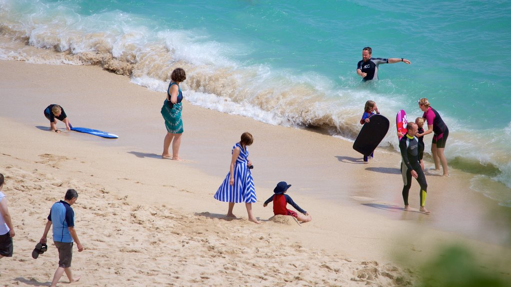 Porthcurno Beach which includes a beach and swimming as well as a small group of people