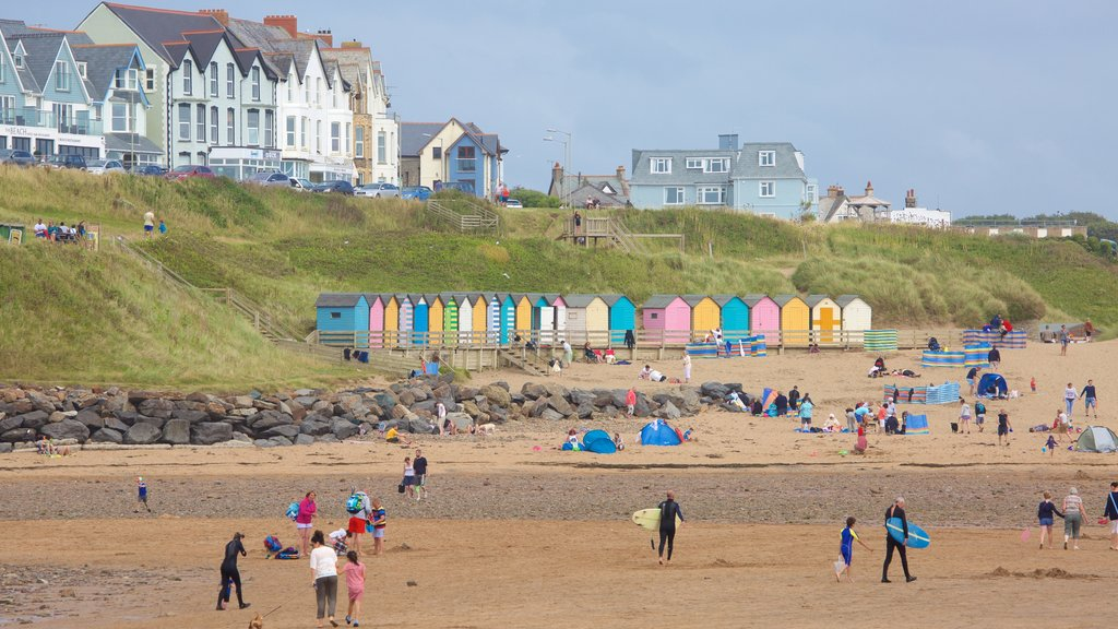 Bude Beach featuring a sandy beach and a coastal town as well as a large group of people