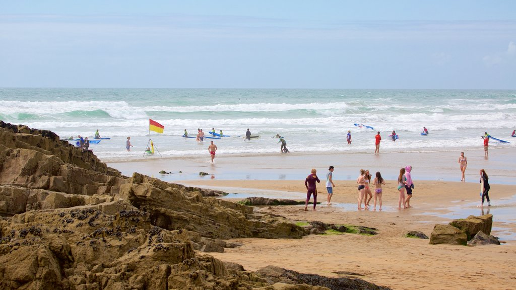 Bude Beach showing a sandy beach and rugged coastline as well as a small group of people