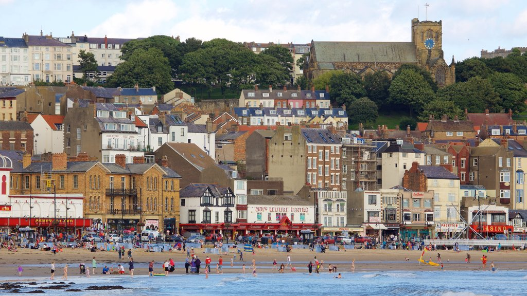 South Bay Beach showing a coastal town and a beach as well as a large group of people