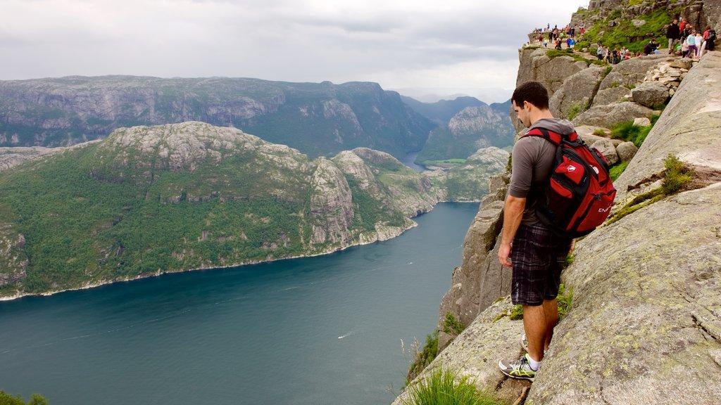 Preikestolen mostrando un lago o abrevadero y montañas y también un hombre